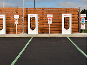 No Parking sign and green pavement markings at Tesla supercharging station